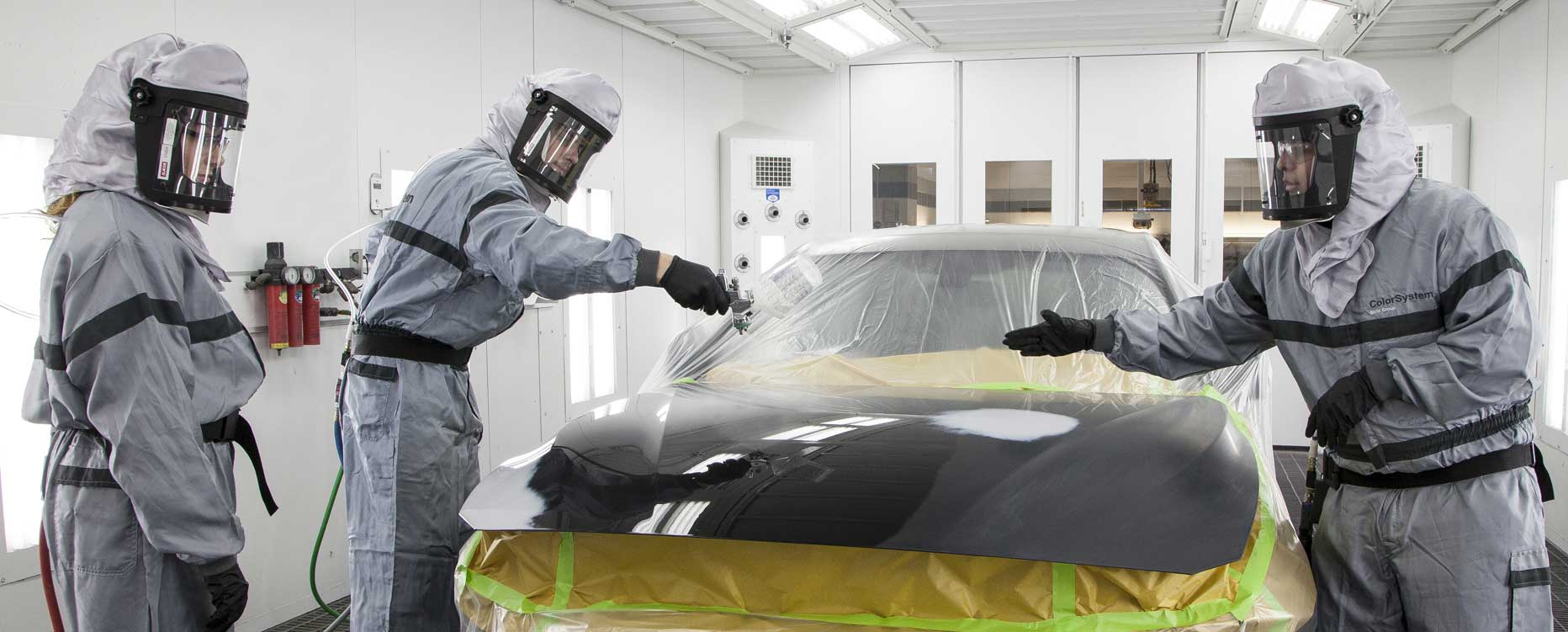 Three technicians spray paint onto the body of a vehicle.