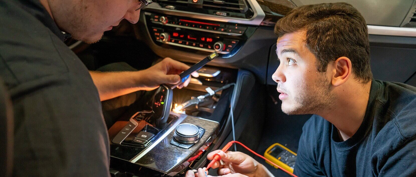 A male technician inspects the dashboard of a car while another technician holds a light so he can see.