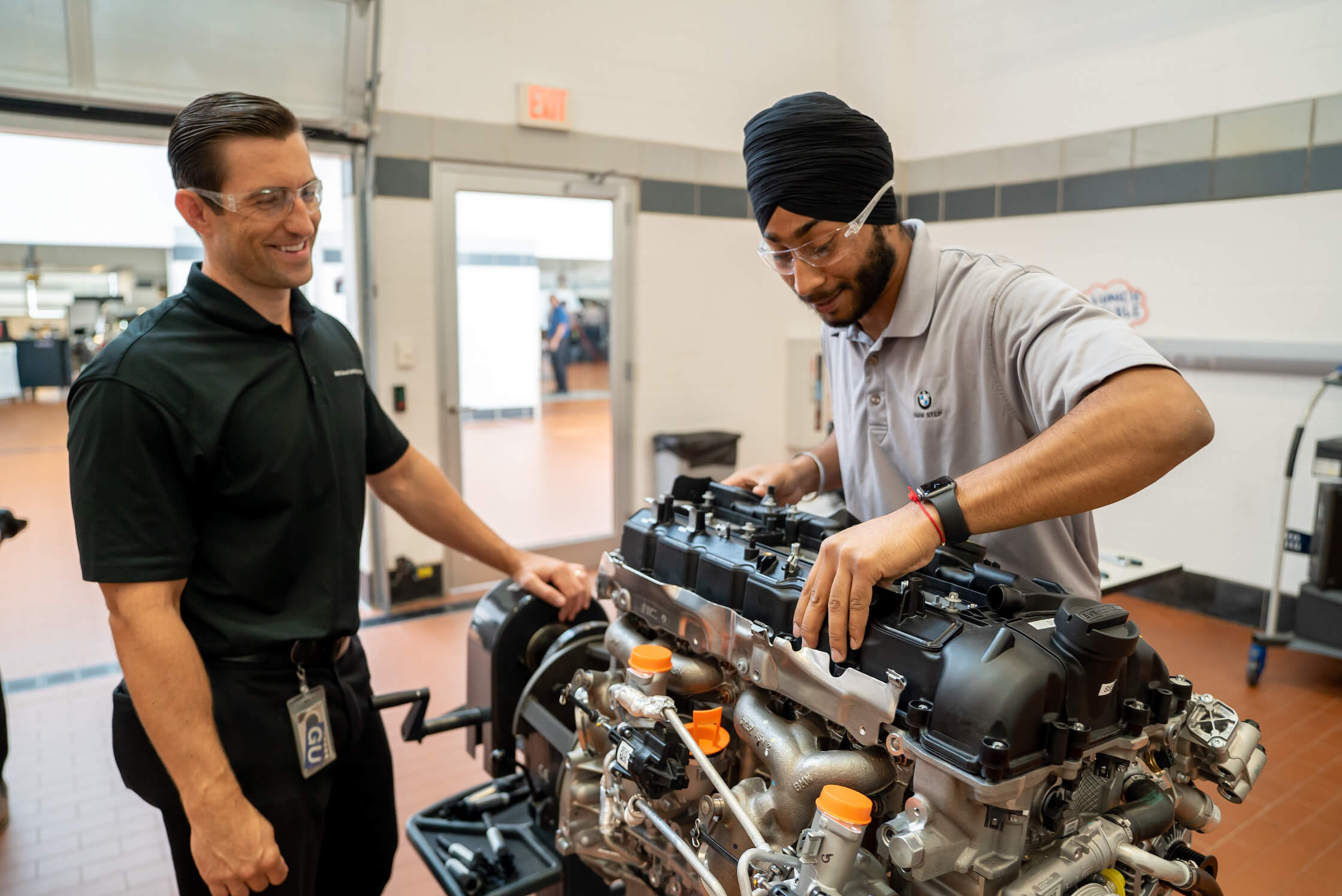 A male technician examines an engine with his STEP instructor supervising.