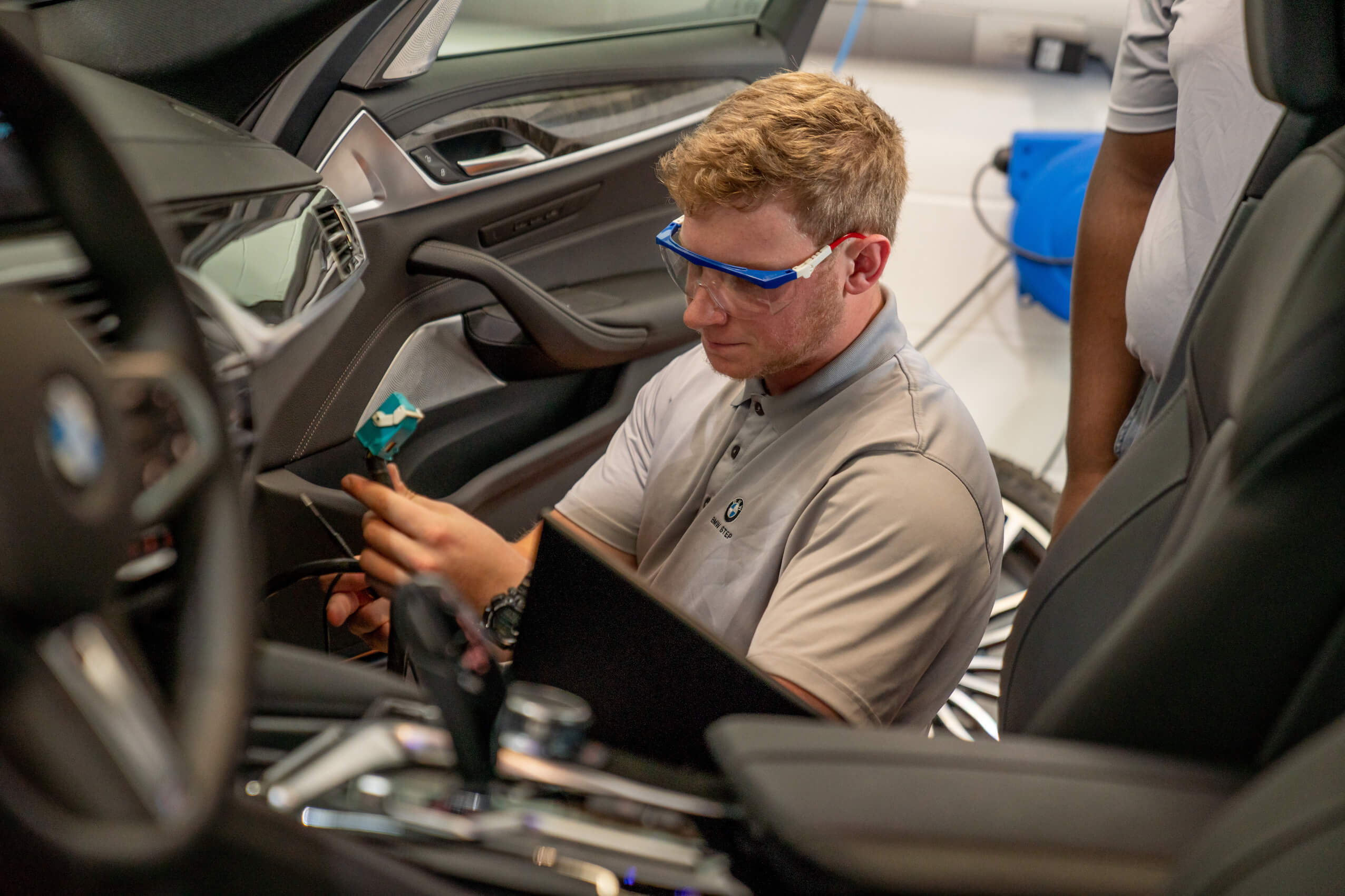 A male technician examines wiring within a vehicle while another male technician observes.