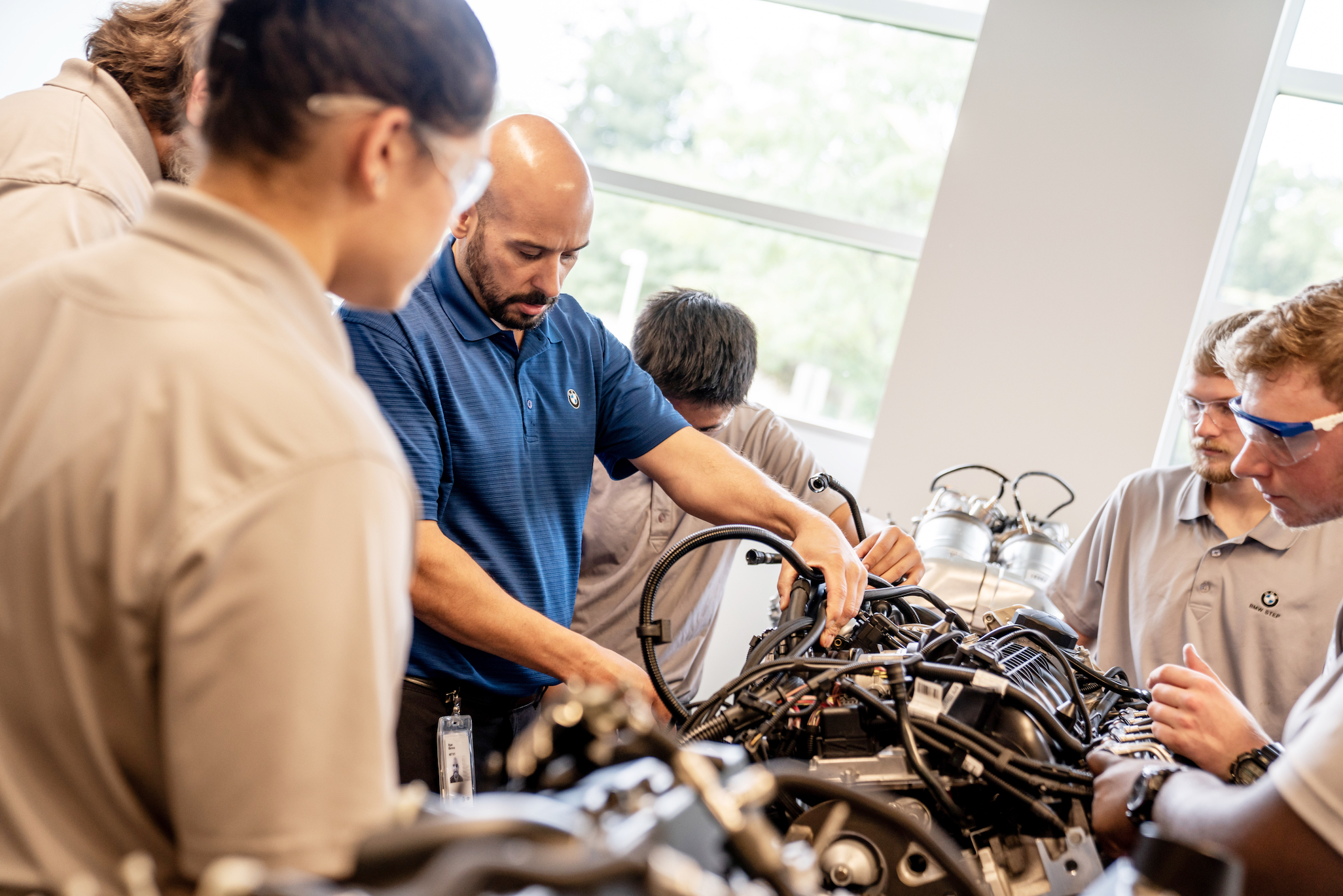 A large group of students watch a STEP instructor examine an engine.