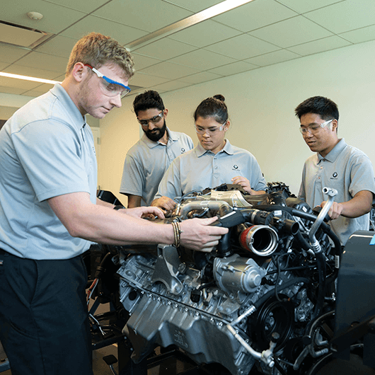 A group of four technicians are inspecting an engine for training.