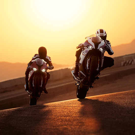 Two motorcyclists ride their motorcycles during the evening. One follows the other for Motorrad Training.